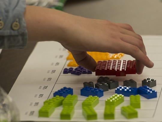 A facilitator moves a block of LEGOs representing different