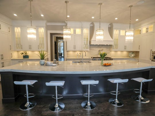 The kitchen as seen from outdoors after the owners removed the  entire back wall in favor of glass doors.The counter is three-inch quartzite, lit by four crystal pendant lights.