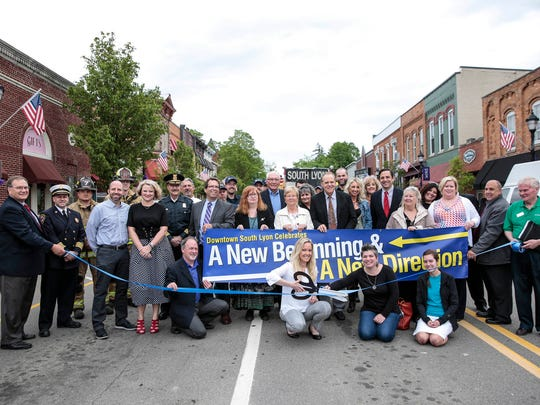 Business owners and public officials from South Lyon pose for a photo before the blue ribbon cutting ceremony on East Lake Street, Tuesday, May 23, 2017 in South Lyon.