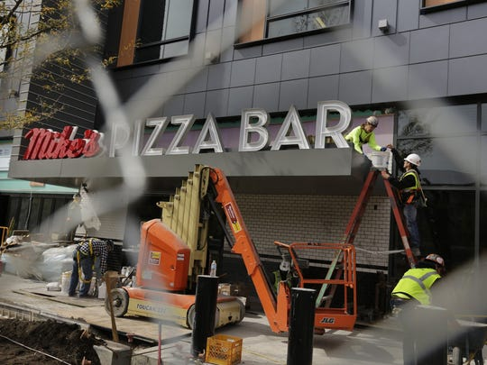 Construction workers put the finishing touches on Mike's Pizza Bar at Little Caesars Arena late last summer.