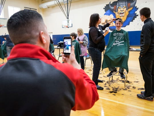 Marysville Middle School eight-grader Teddy Wiley center, has his head shaved during the St. Baldrick's Day fundraiser while his father, Ted, left, and brother Benny watch at Marysville Middle School Friday, March 16.