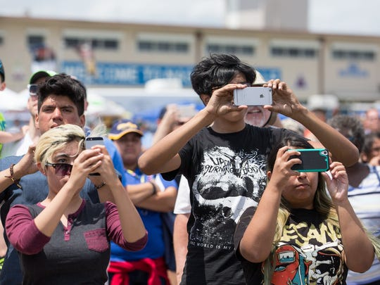 A group of people use their phones to photograph a performance during the Wings Over South Texas air show at the Naval Air Station Kingsville, Saturday, April 9, 2016.
