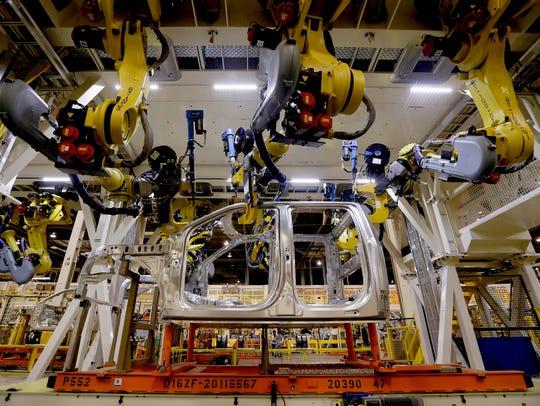 Robots fasten parts on a new 2015 aluminum-alloy body