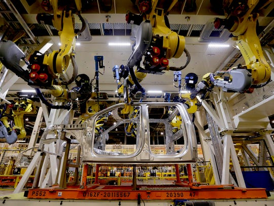 Robots fasten parts on a new 2015 aluminum-alloy body for the Ford F-150 truck in the body shop at the Kansas City Assembly Plant in Claycomo, Mo. in March 2015.