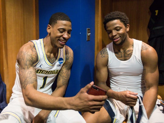 Michigan guard Charles Matthews, left, talks to teammate guard Zavier Simpson as he calls his brother to celebrate defeating Houston in second round of the NCAA tournament in the locker room at INTRUST Bank Arena in Wichita, Kan., Saturday, March 17, 2018.