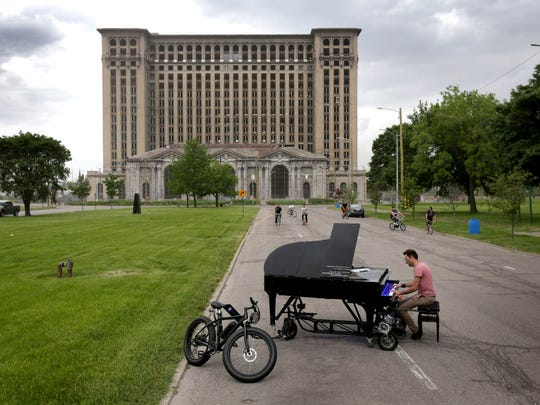 Davide Martello of Germany plays his piano in front of Michigan Central Station during a two day stop in Detroit in May 2015. Martello travels the world playing his piano in public spaces. Within a city he pulls it behind a bicycle and when it is time to move to the next town he loads it up in a trailer that he drives behind his 1991 VW Corrado.