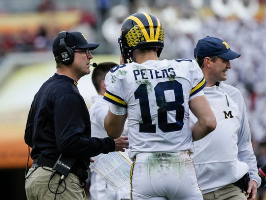 Jim Harbaugh talks to quarterback Brandon Peters during