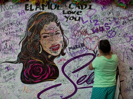 A young girl signs her name on the Selena mural in the Fiesta de la Flor festival's El Mercado, Saturday, May 7, 2016.