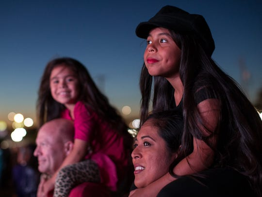A young sits on a woman's shoulder during Erick y Grupo de Massore performs at the first day of the Fiesta de la Flor festival, Friday, May 6,2016.