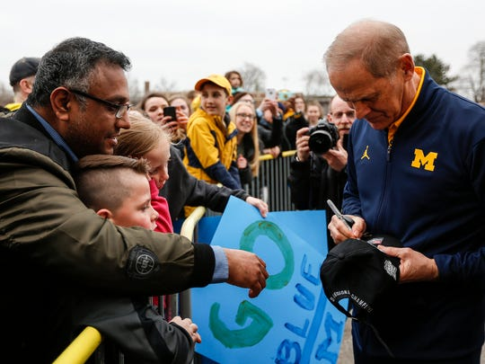Michigan head coach John Beilein signs autographs for