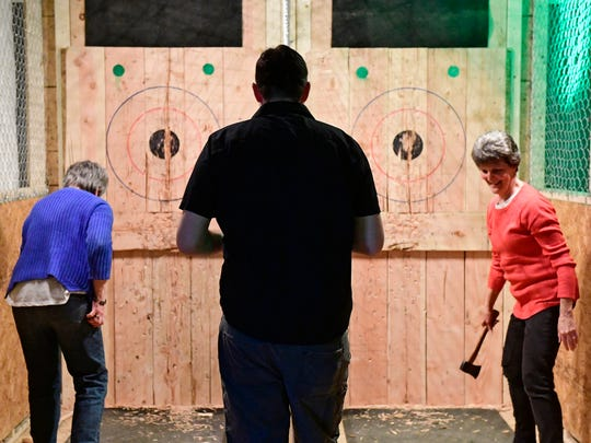 Chris McCleary (left) and Wendy Creamer (right) both from Manheim Township learn how to throw an ax with Ax Trainer Paul Martin at Meduseld Meadery in Lancaster on March 28, 2018. The meadery just opened up an indoor ax-throwing range.