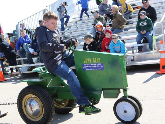 Grant Cumbie, 8, of Omro, works hard as he competes in the kids tractor pull at the Wisconsin Public Service Farm Show in Oshkosh on March 28, 2018.