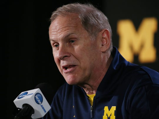 Michigan coach John Beilein speaks with members of