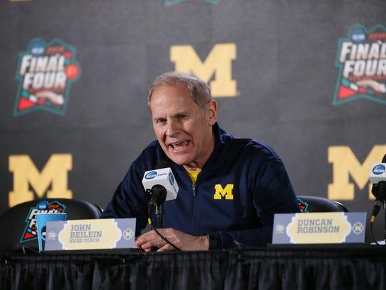 Michigan coach John Beilein speaks with members of