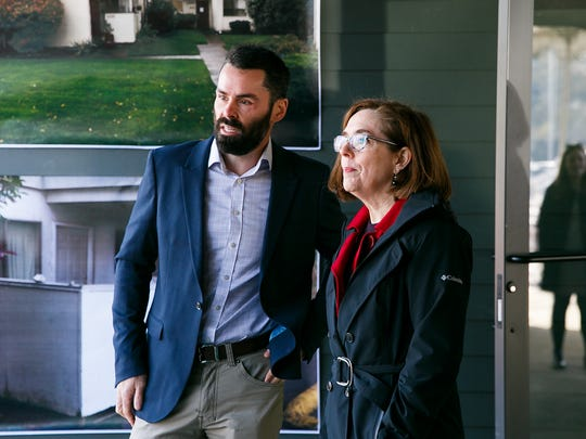 Gov. Kate Brown, right, talks to Eric Paine, Chief