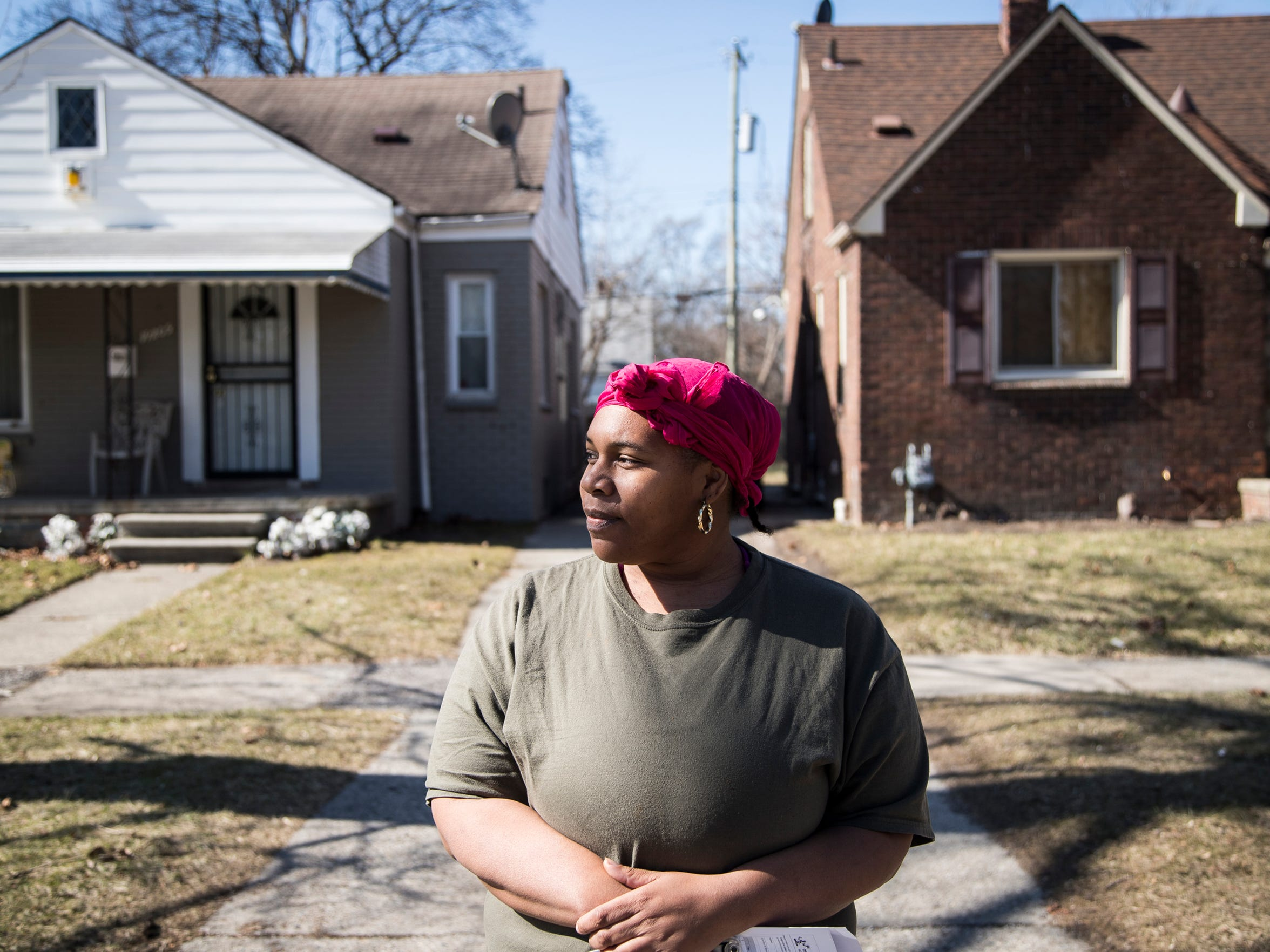 Tasha Hervey of Detroit in front of her house on Murray Hill Street, left, and the house she wanted to buy on the right on Tuesday, February 27, 2018.