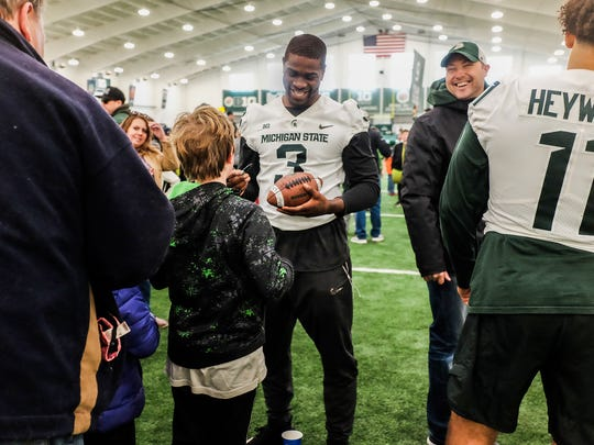 MSU running back LJ Scott signs a football for a kid at MSU's annual youth clinic before the spring game on April 7.