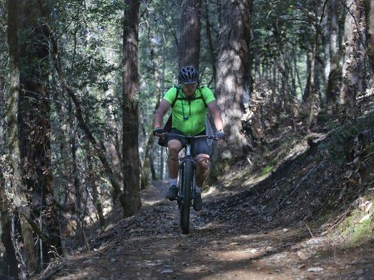 Joel Kwiatkowski rides his mountain bike Monday April 9, along the Shasta-Trinity Trail in Whiskeytown.