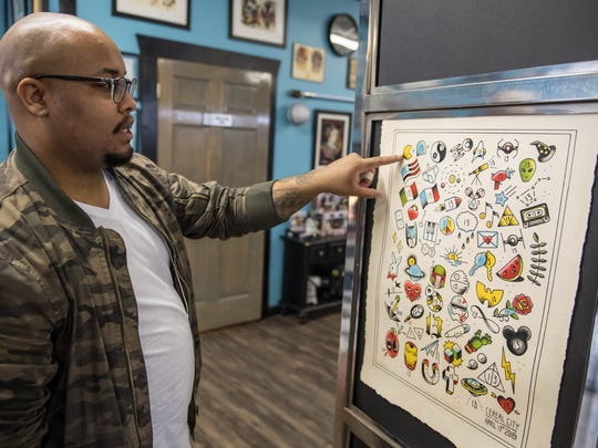 Terin Dickerson shows off the tattoos he designed for the $31 special at Cereal City Tattoo & Piercing on Friday, April 13.
