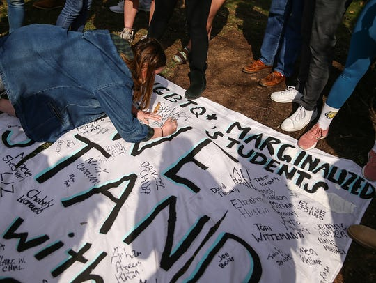 """Students sign a banner that reads """"We stand with you"""" created after racist messages were found on the DePauw University campus."""
