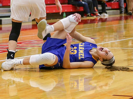 Dilk grimaces in pain after she injured her knee during a sectional semifinals against Noblesville in Fishers.  Dilk returned to the game and Carmel won, 50-45.