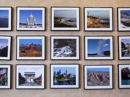 A wall of pictures shot by retired lawyer Rich Bell, seen at his home in McCordsville, Ind., Thursday, April 26, 2018. Bell has filed or threatened hundreds of copyright infringement lawsuits over a photo he shot of the Indianapolis skyline in 2000, pictured center in the bottom row of frames.