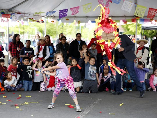 A student from Nellie Muir Elementary School in Woodburn swings at a pinata during the 13th Annual Woodburn Cinco de Mayo Celebration at Chemeketa Community College Woodburn campus in Woodburn, Oregon, Friday, May 4, 2018.