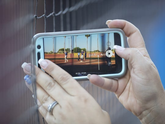 A fan takes a video on a cell phone during the 2A State