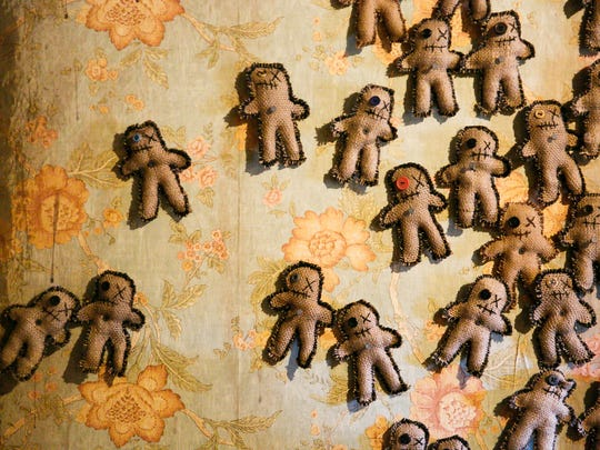 Handmade voodoo dolls are pinned to the wall at a haunted