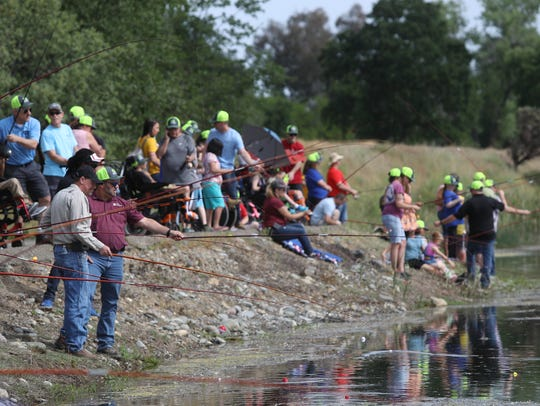 Teachers and volunteers help kids fish Thursday during
