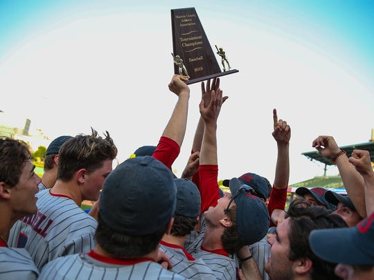 The Roncalli Rebels celebrate with the trophy after defeating Perry Meridian for the Marion County tournament title, final score 5-3, at Victory Field in Indianapolis, Monday, May 14, 2018.