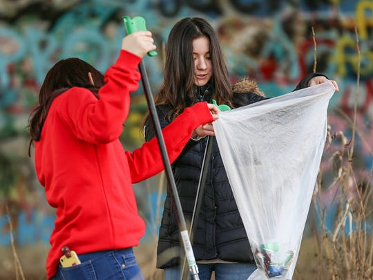 From left, Pike High School students Versha Qazi, 17, and Ginnina Ramirez, 18, help pick up trash during a White River clean-up at Holliday Park in Indianapolis, Thursday, March 22, 2018. The clean-up celebrated World Water Day, and is part of the Partners for the White River initiative to protect and restore the river.