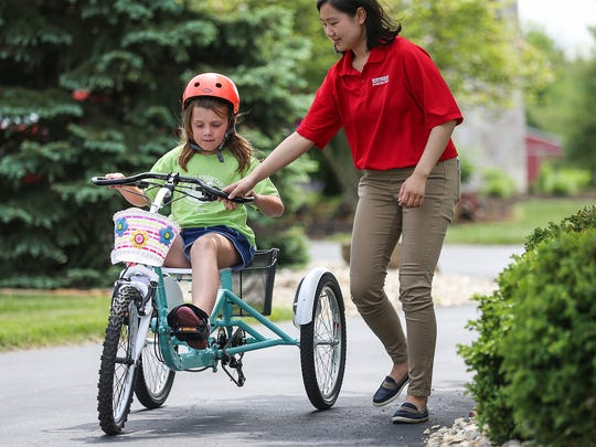 Bella Cates, 9, takes a test ride on her new bike designed