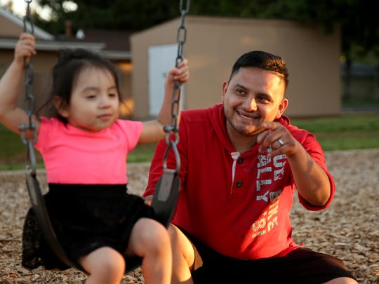 Felipe Vargas-Perez, 25, of Salem, pushes his 2-year-old daughter, Jazlinn Vargas-Rosas, on a swing outside an emergency family shelter at Queen of Peace Catholic Church in Salem on Monday, May 14, 2018.
