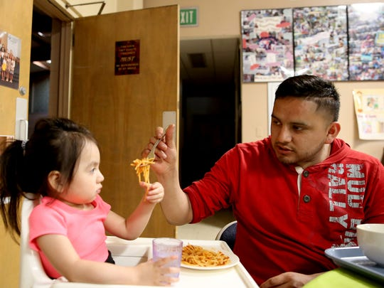 Felipe Vargas-Perez, 25, of Salem, feeds his 2-year-old daughter, Jazlinn Vargas-Rosas, inside an emergency family shelter at Queen of Peace Catholic Church in Salem on Monday, May 14, 2018.