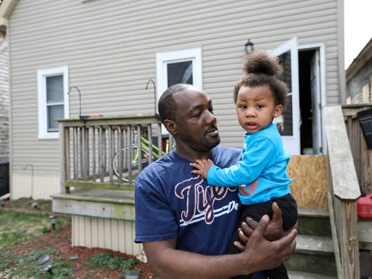 Odale Brown, 39, of Detroit holds his grandson TyJuan Brown, 1, in front of his home on Theodore Street between Dubois and Saint Aubin Streets. He has lived there for 10 years and says the smell from the Detroit Renewable Power facility smells like old cheese and gets so bad sometimes you can taste it.