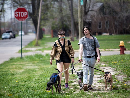 Mary Kate Huffman, 25, of Detroit walks with Josh Brooks, 24, and his dogs Margo, Topo and Peaches, back to his house near the Detroit Renewable Power facility in Detroit on Wednesday, May 2, 2018.