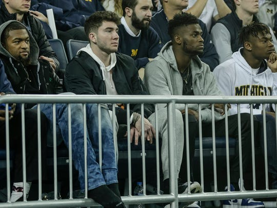 Shea Patterson, second from left, watches a Michigan basketball against UCLA at the Crisler Center in Ann Arbor, Dec. 9, 2017.