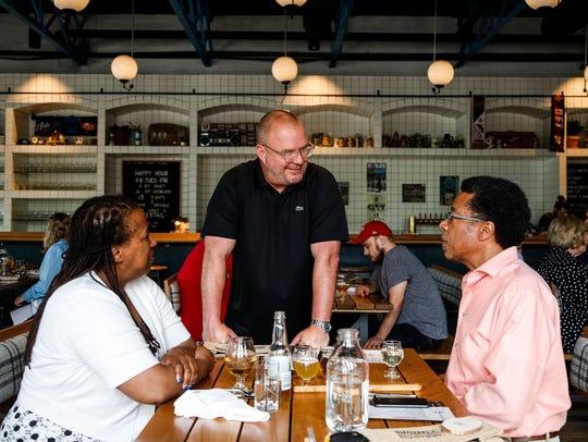 Dan Riley, president of Axle Brewing, center, talks