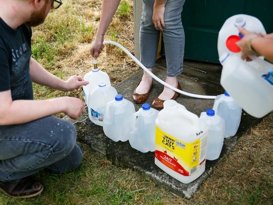Willamette Humane Society staff members fill containers with well water from the shelter's pump house on Wednesday, May 30, 2018. Willamette Humane Society officials said they use about 2,000 gallons of water a day to water the animals, clean and more.