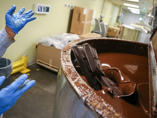 Large blocks of raw chocolate are melted down in the production area of Endangered Species Chocolate in Indianapolis, Tuesday, May 29, 2018. The chocolate will be molded into chocolate bars and bites of various flavors and ingredients, sold in all fifty states and some international markets.