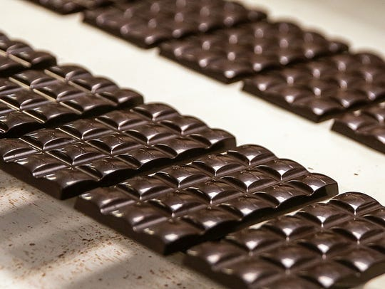 Chocolate bars travel along a conveyer belt at Endangered