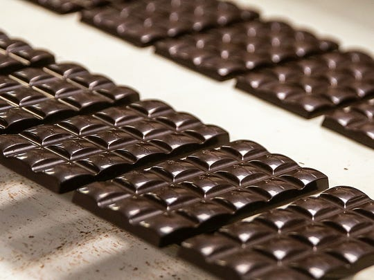 Chocolate bars travel along a conveyer belt at Endangered Species Chocolate in Indianapolis, Tuesday, May 29, 2018. The company relocated to Indianapolis 13 years ago, and has since donated $5 million toward efforts to conserve wildlife and endangered species.