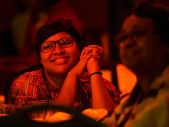 Jazmyne Harris, 23, listens to musicians during a fundraiser