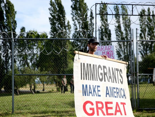 Praise, 53, of Eugene, attends a rally to protest the