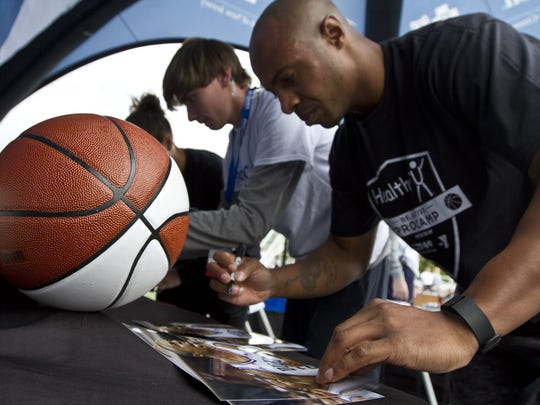 Jay Williams autographs basketballs during an event for kids in 2015.