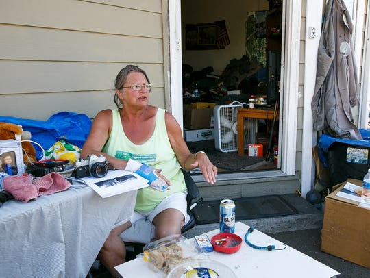 Sherry Husted sits among garage sale items as she talks
