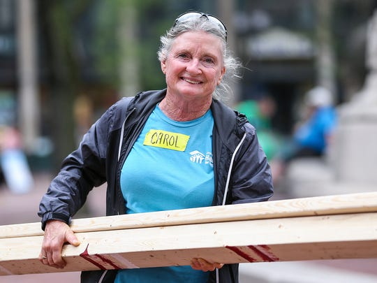 Carol Crisp carries lumber during an inaugural Habitat for Humanity build on Monument Circle in downtown Indianapolis, Friday, June 22, 2018. About 300 volunteers constructed walls for two homes that will stay in Indianapolis and one that will go to South Bend.