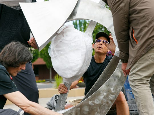 """Hood River artist C.J. Rench helps guide his 11-foot stainless steel sculpture """"Entwined"""" as it is installed at the Salem Convention Center on Tuesday, June 26, 2018."""