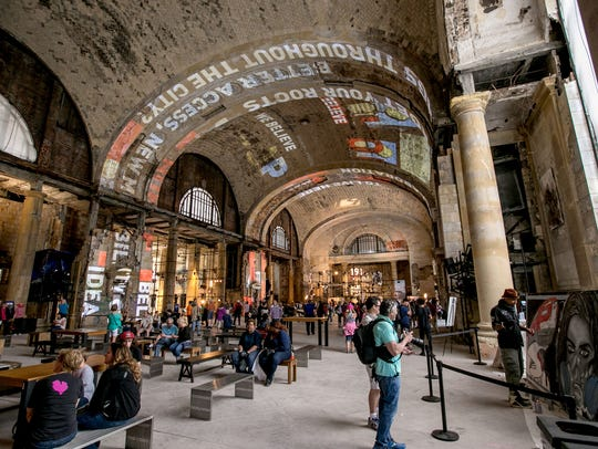 People wander around inside Michigan Central Station